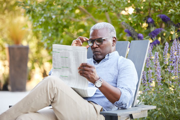 Portrait of African American Senior man reading the newspaper on his patio outside