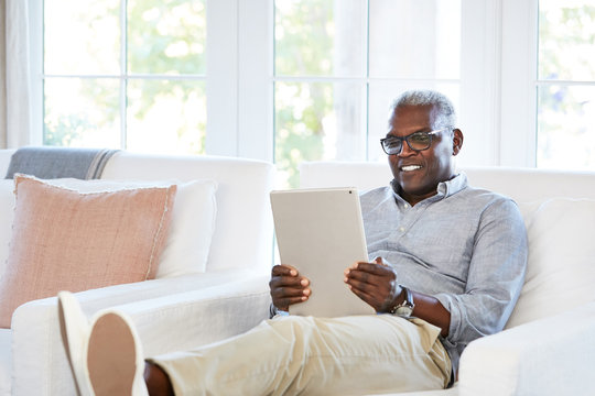 Happy African American Senior man Browsing the internet on a large digital tablet