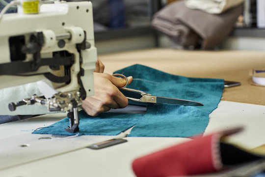 Worker Cutting Fabric By Sewing Machine At Sofa Workshop