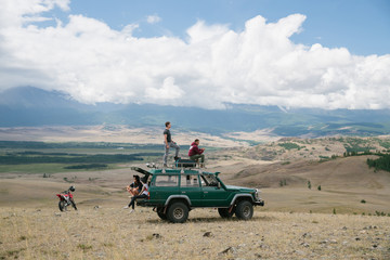 Company of young people resting on the old  jeep parked in wild mountainous area