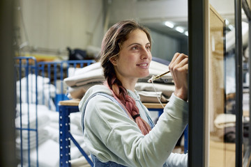 Smiling Worker Writing On Notice Board In Sofa Workshop