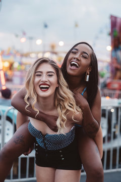Two young female friends having fun at a carnival