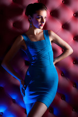 Elegant and beautiful girl in a tight evening dress in blue on a red relief background in the studio