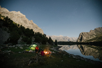 couple camping outdoors in a green tent beside a lake with a campfire at night