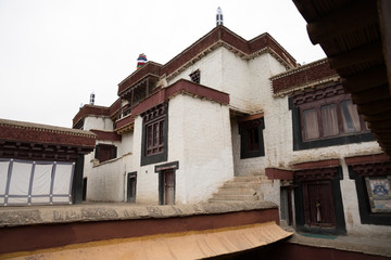 White Tibet Buddhism monastery on the mount during a day from below