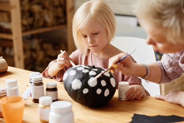 Girl decorating pumpkin for Halloween