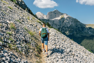 Young man with backpack hiking into the rocky mountains on a trail