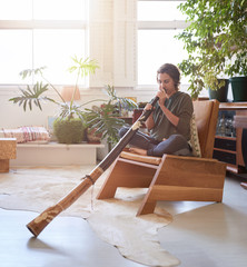Young woman didgeridoo player practising at home