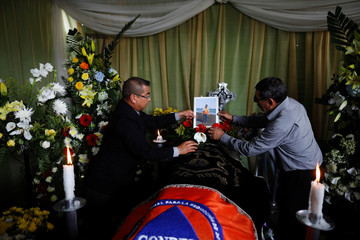 Family members of Juan Fernando Galindo, member of the National Coordinator for Disasters Reduction (CONRED), set a picture on his coffin during his wake in Alotenango