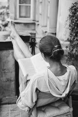 Woman reading a book at the balcony