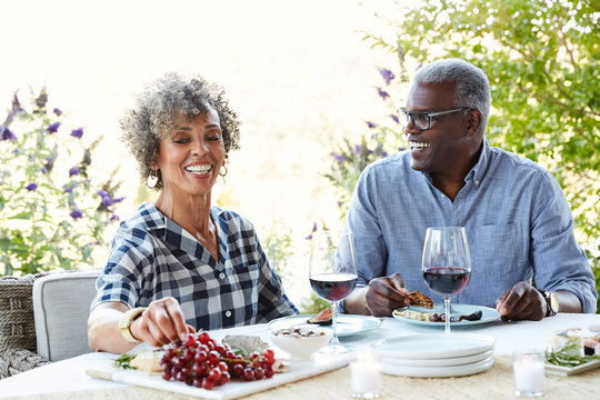 Mature African American couple drinking wine and eating lunch outdoors on the patio at home