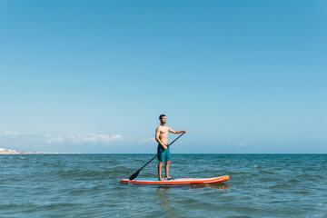Shirtless man on paddleboard