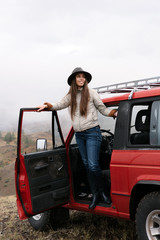 Woman posing in car while traveling