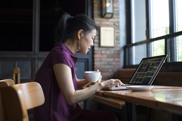 One senior asian woman working with laptop in cafe