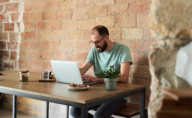 Portrait of busy programmer with beard in glasses working on his laptop at desk with bakery and green plant in pot. Red brick wall in background. Copyspace.