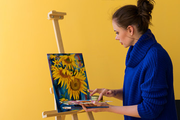 Girl artist paints sunflowers oil paints on canvas. She is wearing blue sweater. Woman is holding brush and palette with paints. She mixes colors with her fingers.