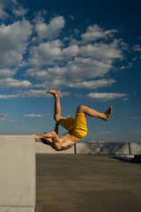 Tricking on street. Martial arts and parkour elements. Man flips back barefoot. Taken from low angle against sky.
