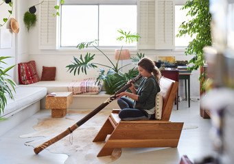 Hippy woman playing didgeridoo at home