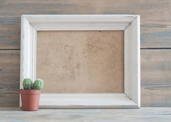 photo frame on old wooden table with cactus