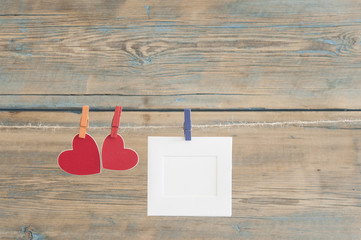 blank instant photos hanging on the clothesline with red heart