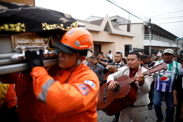Musicians perform during the funeral of Juan Fernando Galindo, member of the National Coordinator for Disasters Reduction (CONRED), in Alotenango