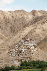 Panoramic photo from below of Tibet Buddhism monastery and mountain village at sun light