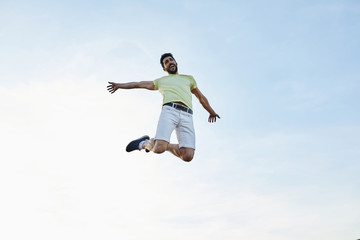 Happy man jumping over sky.