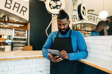 Portrait of a young black man using digital tablet in a pastrami sandwich bar.