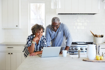 Senior African American on computer in the kitchen together