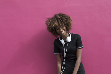 Young woman with headphones in front of a purple wall.