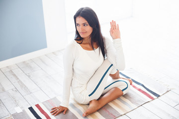 Charming young woman in a gymnastic suit doing yoga exercises Marichiçana sitting on a rug in wooden floor in a gym