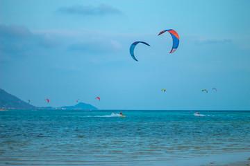 Tourists enjoy Kitesurfer surfing in the sea.