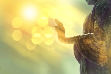 Poster Buddha hand of buddha statue with yellow bokeh background, light of wisdom and concentration concept