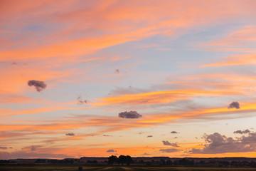 Orange summer sunset over a homestead in Montana.