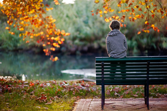 Boy perched on a park bench in a park in autumn