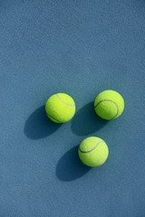 Three tennis balls on court
