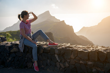 tourist girl looking at mountains and sunset