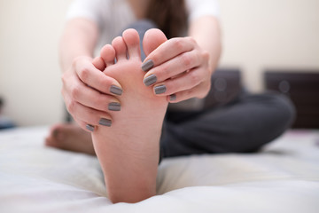 Young woman massaging her pain foot. Health care concept.