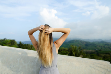 Young relaxed girl standing in mountains background, wearing grey shirt. Concept of nature and traveling, summer vacations.