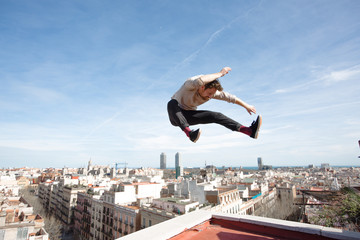 Man jumping in a playful way at the top  of a building in Barcelona