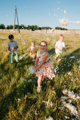 Group of cute children playing outdoors with feathers and running on the field of herbs. Older girl smiling and looking at camera