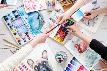 creative leisure. painting hobby. artful personalities working together. watercolors and drawings scattered on the table