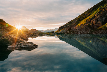 Alpine Sunrise - First Sunrays Hitting Lake and Surrounding Hills