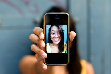 Asiatic woman smiling and taking a selfie with her smartphone