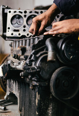 Mechanic fixing an engine for a head gasket repair in a garage.
