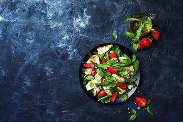 Delicious salad with arugula, strawberries and grilled chicken, top view