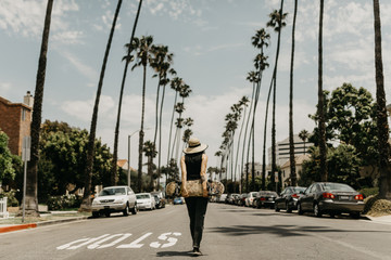 Woman skateboarder holding skateboard behind her