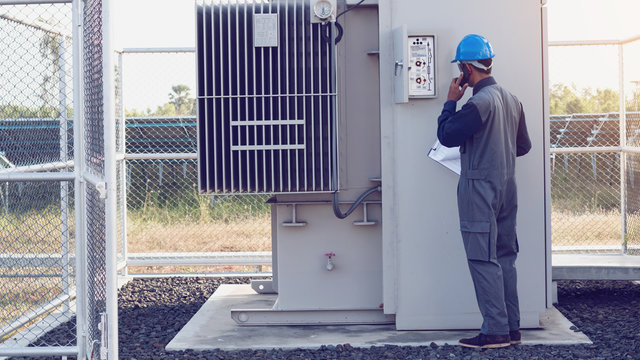 engineer or electrician working on checking and maintenance equipment at green energy solar power plant; checking status step up transformer high voltage at transformer yard