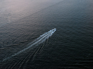A motorboat cruising down the Hudson river from above.