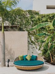 Rattan sofa seat by palm trees